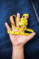 main avec ruban à mesurer. photo