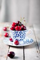 cerise fraîche dans une tasse en céramique bleue photo