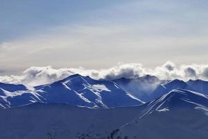 montagnes d'hiver du soir et nuages du soleil photo