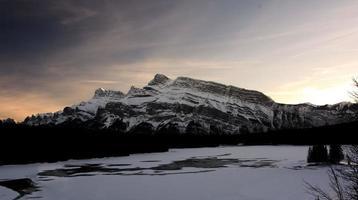 coucher de soleil derrière une montagne photo