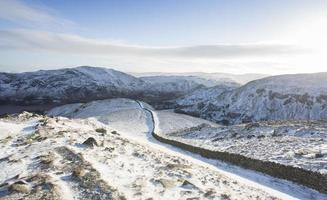 long chemin couvert de neige et mur menant aux montagnes photo