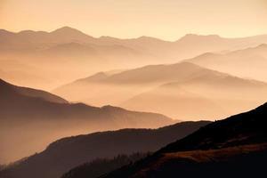 Vue paysage des collines de montagne brumeuses au coucher du soleil photo