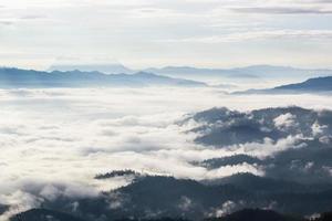 Montagnes en couches brumeuses au lever du soleil photo