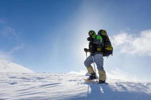 Backpacker homme marchant dans les montagnes d'hiver aux beaux jours photo