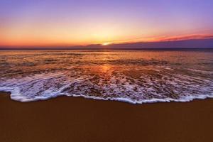 lever du soleil et vagues brillantes dans l'océan photo