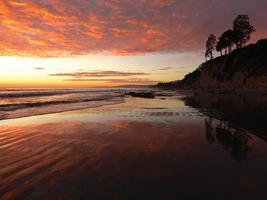 Océan à marée basse coucher de soleil reflétant sur le fond marin. photo
