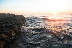 vague de l'océan au coucher du soleil photo