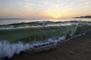 vague se brisant sur la plage océan coucher de soleil photo