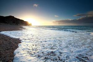 vagues de l'océan sur la plage rocheuse au coucher du soleil photo