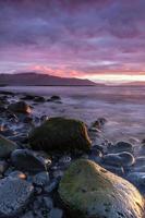 Coucher de soleil sur l'océan coloré sur la plage volcanique en Islande
