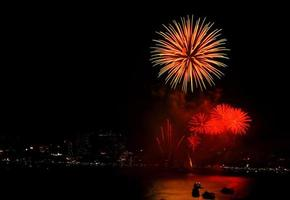 feu d'artifice sur la ville la nuit avec reflet dans l'eau
