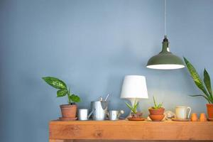 lampe de table et petit pot de fleurs sur meuble en bois
