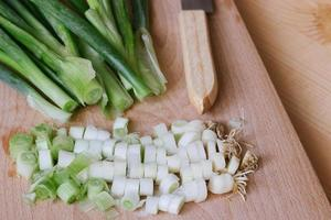 Oignons verts hachés sur une planche à découper en bois