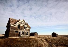 Maison de ferme abandonnée dans la prairie photo
