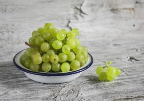 Raisins verts frais dans un bol en émail blanc photo