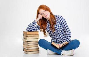 fille souriante assise et s'appuyant sur la pile de livres photo