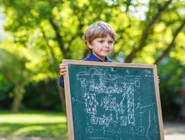 petit garçon au tableau noir faisant la présentation