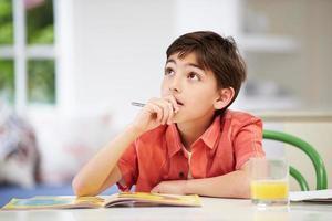 garçon hispanique, faire ses devoirs dans la cuisine photo