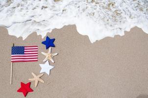 drapeau américain avec des étoiles de mer sur la plage de sable photo