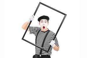 artiste mime tenant un grand cadre photo