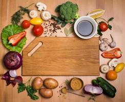 divers légumes et épices autour d'une planche à découper vide. vue de dessus.
