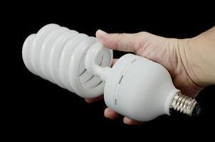 Main tenant une ampoule à économie d'énergie, isolée sur fond noir