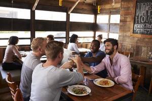 Quatre amis masculins faisant un toast à une table dans un restaurant