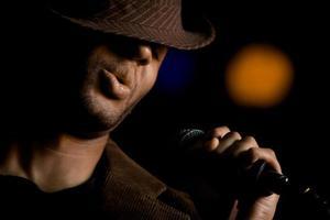 chanteur afro-américain portant un fedora au micro photo