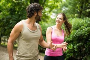 souriant heureux couple en cours d'exécution dans un parc photo