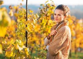 Portrait de jeune femme réfléchie debout dans le vignoble d'automne