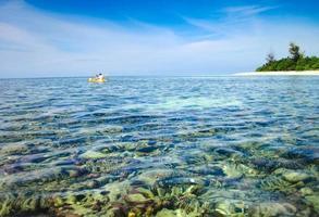 père et fils en kayak à côté d'une belle île de corail