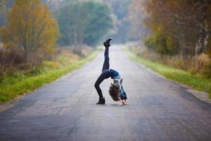 jeune fille fait le grand écart sur la route