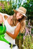 Femme jardinier arrosage des fleurs dans le jardin