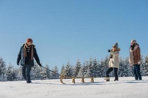 Jeune homme tirant la campagne d'hiver de traîneau à neige