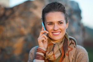 Heureuse jeune femme en soirée d'automne à l'extérieur parler téléphone portable