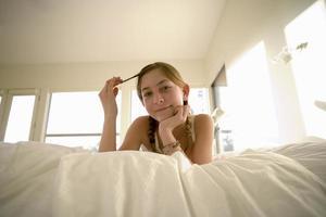 fille sur le devant sur le lit, cheveux tourbillonnant dans les doigts