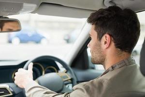 jeune homme regardant vers l'avant en conduisant photo