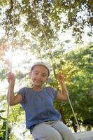 heureuse petite fille sur une balançoire dans le parc photo