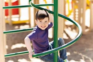 Heureux petit garçon grimpant sur une aire de jeux pour enfants
