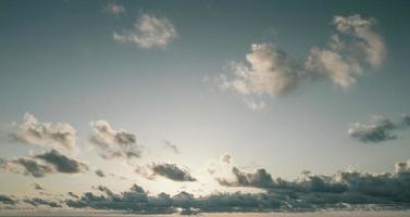 ciel bleu avec des nuages duveteux au lever du soleil