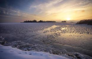 paysage d'hiver avec lac et ciel de feu au coucher du soleil. photo