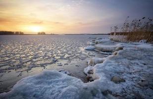 beau paysage d'hiver avec lac gelé et ciel coucher de soleil. photo