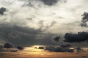 coucher de soleil avec nuages gris et derniers rayons de soleil photo