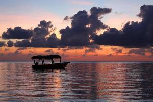 silhouette d'un bateau au lever du soleil photo