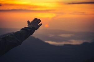toucher la main de l'homme concept de ciel et mode de vie de voyage au coucher du soleil photo