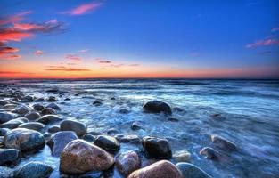 coucher de soleil sur la mer baltique. plage de galets à rozewie photo