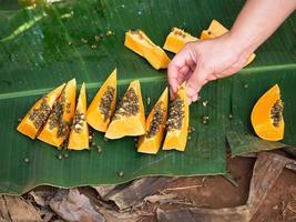Des tranches de papaye mûre reposent sur les feuilles de palmiers