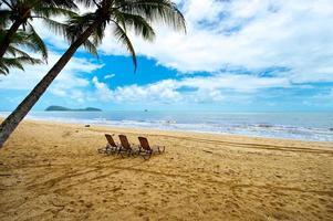 trois chaises longues sur une plage