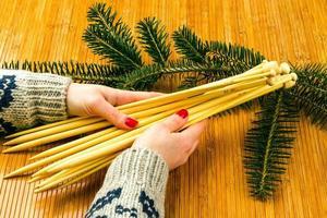 mains de la jeune femme tenant des aiguilles à tricoter photo