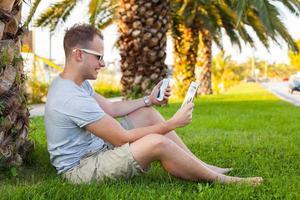 jeune touriste assis sous le palmier avec smartphone et tablette.